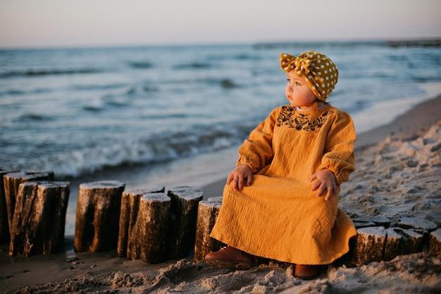 Linda criança sentada no quebra-mar na praia do mar báltico na hora do nascer do sol