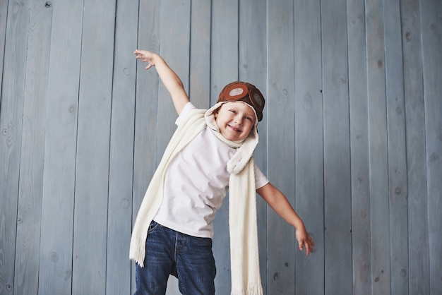 Linda criança sorridente no capacete sobre um fundo azul, brincando com um avião. piloto vintage