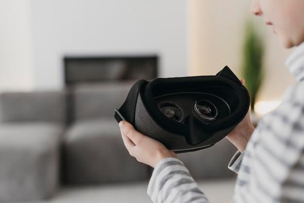 Linda criança usando fone de ouvido de realidade virtual com fundo desfocado