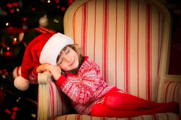 Linda criança vestida com chapéu de papai noel. bebê engraçado dormindo contra a árvore de natal. conceito de férias de natal