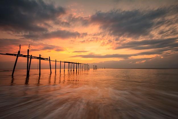 Linda da ponte velha e ondas no mar durante a hora por do sol