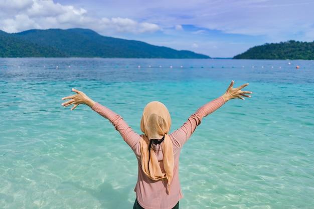 Linda de feliz jovem braço estendido na ilha de tailândia lipe com a água do mar azul-turquesa