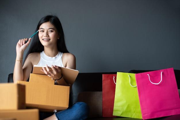 Linda de retrato asiático jovem trabalhando laptop on-line e pensando para marketing