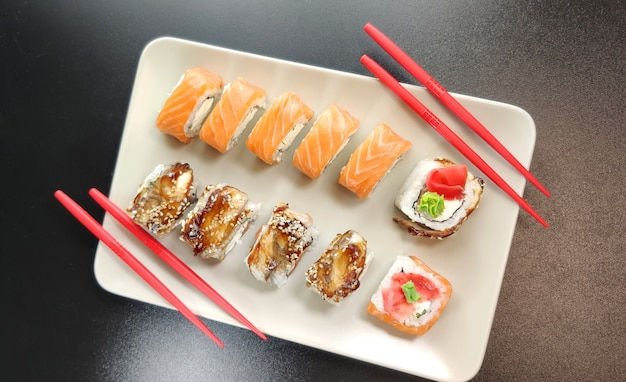 Linda de sushi rola com pauzinhos vermelhos em um prato.