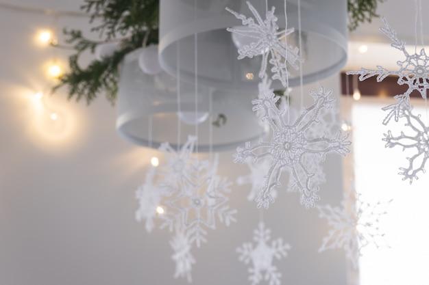 Linda decoração de interiores de inverno flocos de neve de malha branca pendurados em um lustre no natal