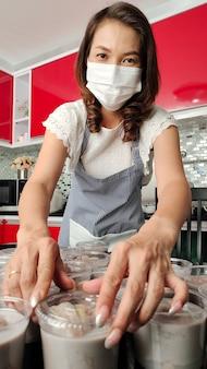 Linda dona de casa asiática usando máscara protetora prepara um conjunto de banana no leite de coco, famosa sobremesa nativa do estilo tailandês, para venda e entrega aos clientes para renda durante a quarentena do coronavírus.