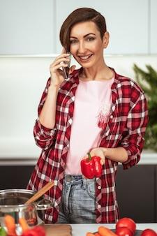 Linda dona de casa com um penteado curto atendendo uma ligação