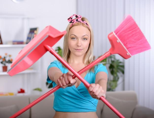 Linda dona de casa com uma vassoura para limpeza em casa
