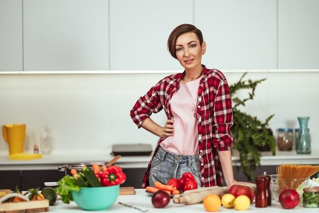 Linda dona de casa cortando ingredientes na mesa cozinhando um almoço em pé na cozinha com uma mão