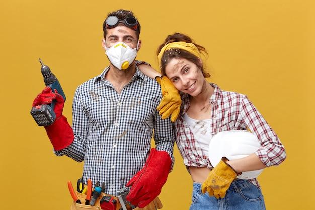 Linda dona de casa feminina ajudando o marido na construção, vestindo camisa quadriculada, segurando o capacete branco apoiado em seu ombro, tendo bom humor, sendo feliz em ajudá-lo. pessoas e relacionamentos