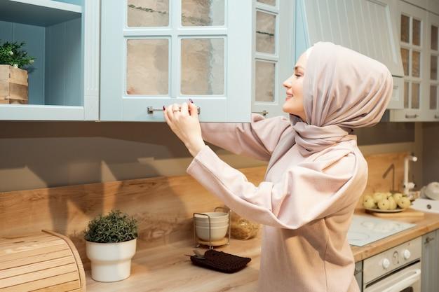 Linda dona de casa muçulmana em hijab abre o armário da cozinha na vista lateral da cozinha moderna