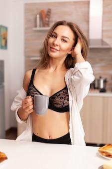 Linda dona de casa sorrindo durante o café da manhã na cozinha de casa usando lingerie preta sexy. jovem mulher atraente com tatuagens em lingerie sedutora, segurando uma xícara de chá relaxante na cozinha sorrindo.