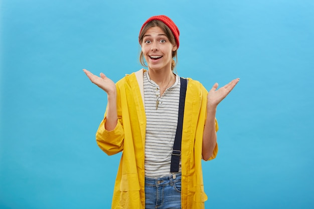 Linda dona de casa usando chapéu vermelho, jaqueta amarela e macacão jeans, encolhendo os ombros, erguendo as sobrancelhas em surpresa, abrindo a boca e sentindo-se maravilhada posando sobre uma parede azul com espaço de cópia