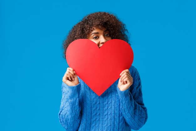 Linda e adorável garota afro-americana corada, com corte de cabelo afro, no suéter, escondendo o rosto atrás de um grande coração vermelho e espiando com alegria, a parede azul.