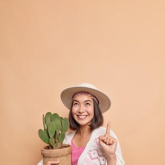 Linda e alegre mulher asiática aponta o dedo indicador para cima segurando um vaso de cacto vestido com roupas da moda, demonstrando um espaço em branco para seu conteúdo de publicidade