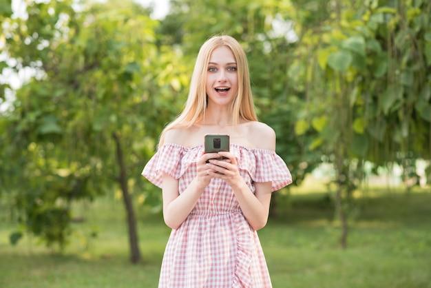 Linda e atraente loira segurando um smartphone. emoção positiva de surpresa. trabalhador autonomo.