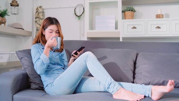 Linda e atraente mulher asiática sorridente usando smartphone segurando uma xícara de café quente