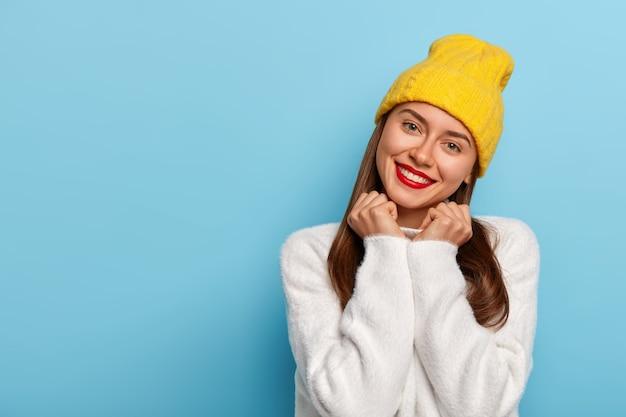 Linda e bonita jovem inclina a cabeça, tem olhar terno, sorri feliz, usa batom vermelho, maquiagem mínima, usa chapéu amarelo e suéter branco confortável, isolado sobre fundo azul