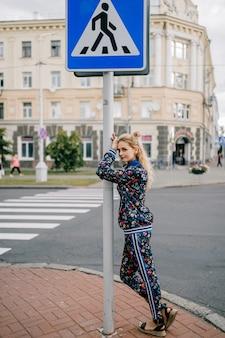 Linda e elegante modelo loira em um terno colorido, posando na rua