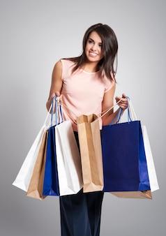 Linda e elegante mulher viciada em compras com sacolas de compras