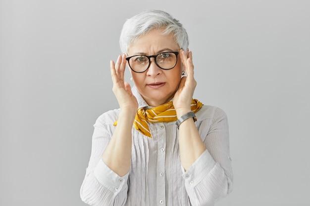 Linda e elegante senhora europeia de idade madura vestindo blusa, relógio de pulso e lenço de seda ajustando os óculos, com expressão concentrada e séria, ouvindo com atenção