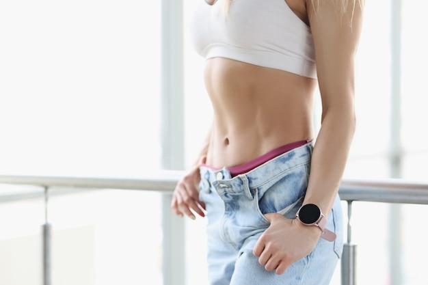 Linda e estimulada imprensa de mulher jovem em jeans conceito de músculos abdominais