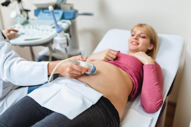 Linda e feliz futura mãe fazendo ultrassom na clínica pré-natal.
