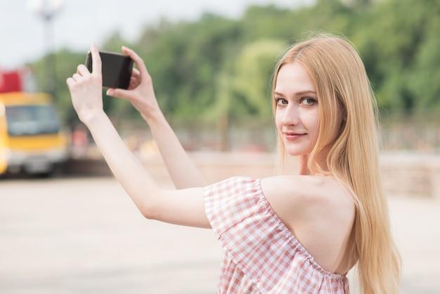 Linda e feliz garota loira caucasiana segurando um smartphone nas mãos e tirando foto