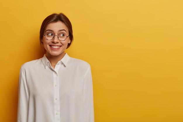 Linda e feliz jovem europeia com sorriso carinhoso, olha de lado, feliz por vir na reunião formal, usa óculos redondos transparentes e camisa branca elegante, posa contra a parede amarela