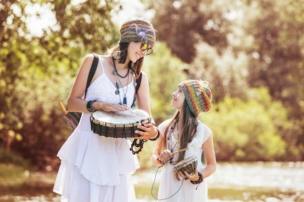Linda e feliz jovem mãe e filha na natureza com instrumentos musicais juntos