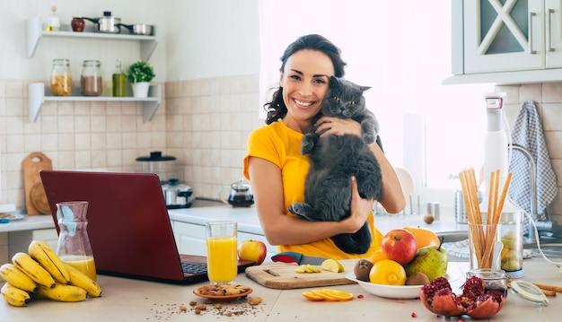 Linda e feliz jovem morena com seu gato na cozinha em casa
