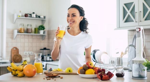 Linda e feliz jovem morena na cozinha em casa está bebendo suco de laranja