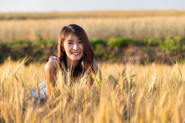 Linda e feliz mulher asiática, curtindo a vida no campo de cevada ao pôr do sol.