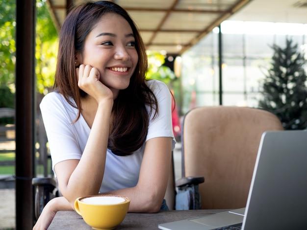 Linda e fofa mulher asiática sorri brilhantemente
