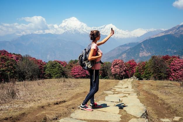 Linda e jovem garota fazendo selfie e fotografando a paisagem em caminhadas nas montanhas. o conceito de recreação ativa e turismo na montanha. trekking no nepal, himalaia