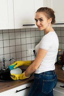 Linda e jovem garota lava pratos na pia. o conceito de limpeza de primavera e empresa de limpeza