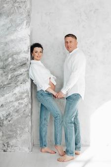 Linda e jovem mãe de camisa branca e calça jeans azul tocando as mãos com o marido