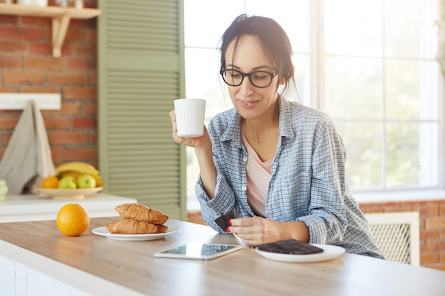 Linda e jovem modelo feminina usa óculos e camisa, toma café com croissants e chocolate amargo, toma café da manhã antes do trabalho,