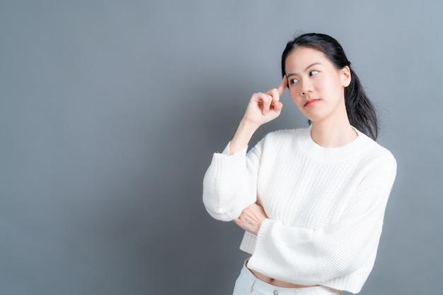 Linda e jovem mulher asiática pensando em fundo cinza