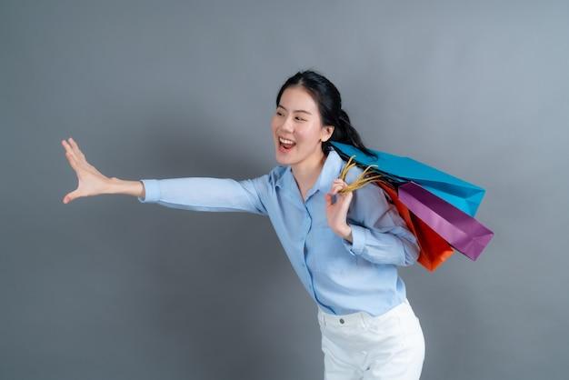 Linda e jovem mulher asiática segurando sacolas de compras em um fundo cinza