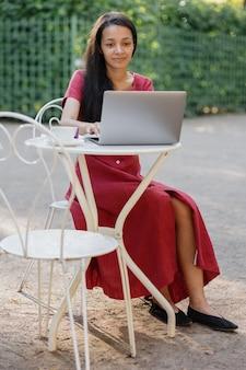 Linda e jovem mulher milenar africana em um lugar público trabalhando em um laptop afro-americano
