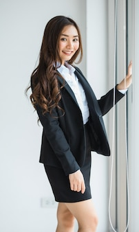 Linda e linda morena empresário feminino asiático lindo parecia em terno preto elegante em pé no escritório e olhando para a câmera com uma cara feliz amigável e positiva.