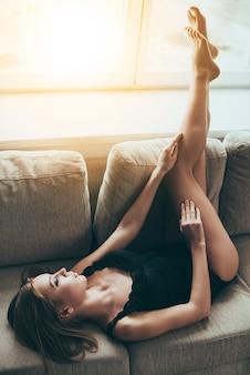 Linda e sensual. mulher jovem e bonita em lingerie preta mantendo os olhos fechados enquanto estava deitada no sofá em casa