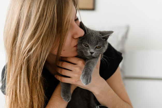 Linda e sexy garota deitada na cama com um pijama caseiro, segurando um feliz gatinho escocês cinza nos braços.