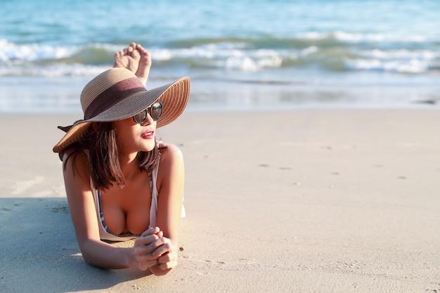 Linda e sexy menina asiática com chapéu deitado na praia