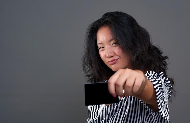 Linda e simpática jovem morena chinesa oferecendo um cartão com um olhar direto e desafiador