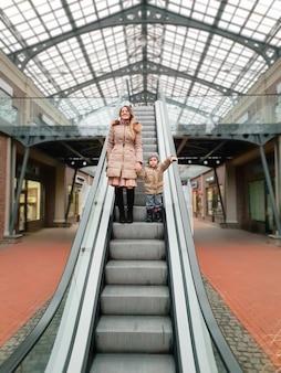 Linda e sorridente jovem mãe segurando seu filho pequeno enquanto está de pé na escada rolante de um shopping center