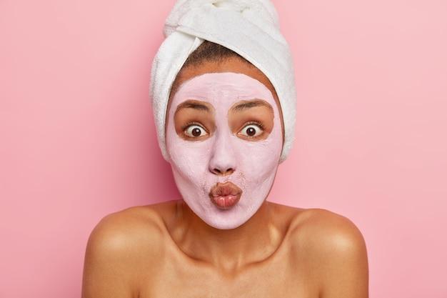 Linda e surpresa modelo feminina aplica máscara de argila, mantém os lábios dobrados, usa toalha branca macia na cabeça branca, tem regime de beleza diário