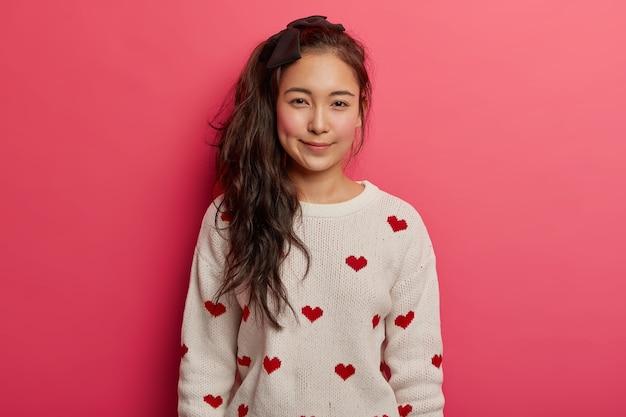 Linda e terna menina asiática com rabo de cavalo longo, bochechas vermelhas, usa um macacão confortável com corações e fica de pé contra um fundo rosa