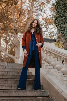 Linda elegante e sorridente mulher magra com cabelo encaracolado andando nas escadas da rua, vestida com um casaco marrom quente e terno azul, outono na moda estilo de rua
